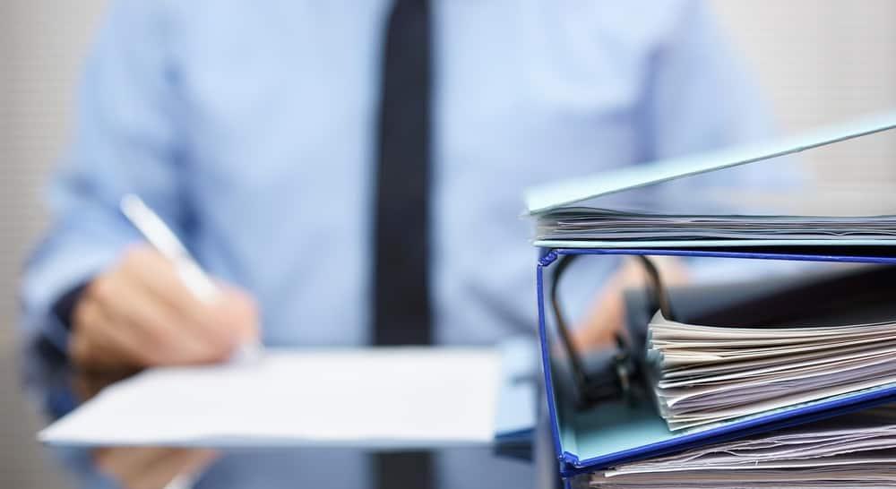 Мужчина, сидящий за столом с документами