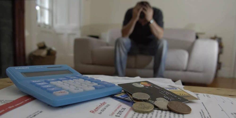 Мужчина, сидящий на диване напротив столика с деньгами